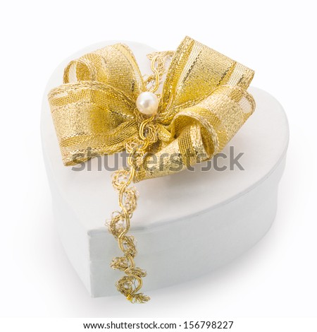 Heart shaped white cardboard gift box tied with an elegant gold bow, braid and pearl for surprising a loved one on Christmas, Valentines, birthday or an anniversary - stock photo