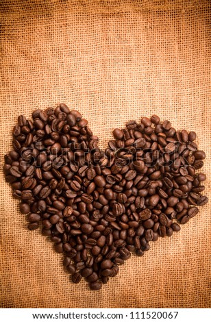 Heart sign by coffee bean on burlap texture - stock photo