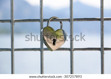 Heart (silver) shaped love padlock - beautiful wedding day custom. Shallow depth of field - stock photo