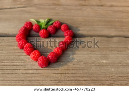 Heart sweet red raspberries with green mint leaf on wooden table - stock photo