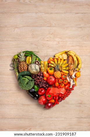 Heart symbol. Fruits diet concept. Healthy eating concept / food photography of heart made from different fruits and vegetables on wooden table  - stock photo