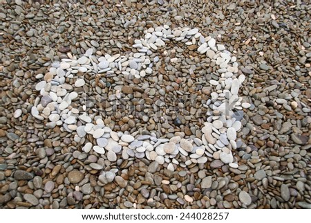 heart symbol made of pebbles on the beach - stock photo