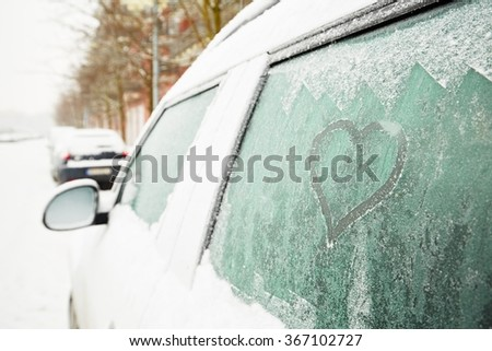 Heart symbol on frozen window of the car - stock photo