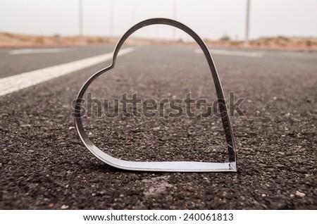 Heart Symbol on the Grainy Asphalt Texture. Love for Travel Concept - stock photo