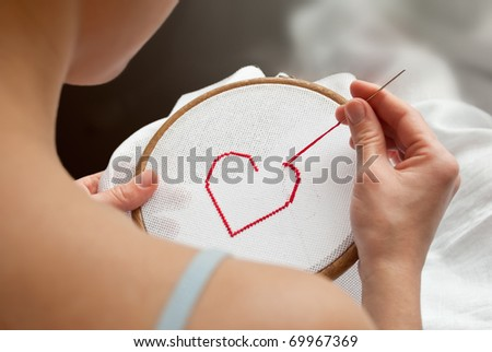 heart (valentine gift), being embroidered on canvas in tambour by female's hands - stock photo
