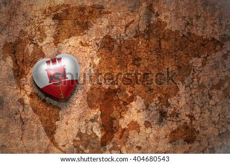 heart with national flag of gibraltar on a vintage world map crack paper background. concept - stock photo