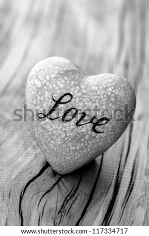 Heart with word ''love'' on wooden wall, black and white photo. - stock photo