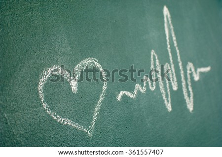 Heartbeat sign and love heart on a blackboard. - stock photo