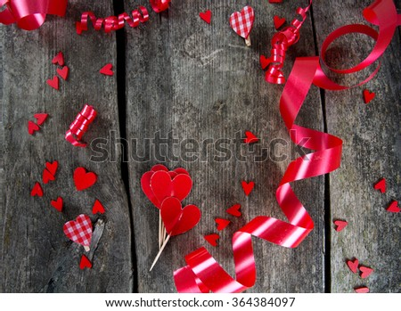 hearts and ribbons on wooden surface - stock photo
