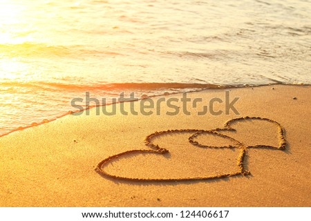 Hearts drawn on the sand of a beach - stock photo