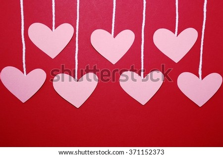 Hearts hanging by string on a red background, can be used for a Valentine's Day or Mother's Day project - stock photo