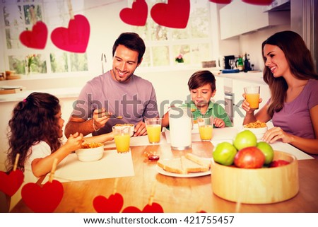 Hearts hanging on a line against family eating healthy breakfast - stock photo