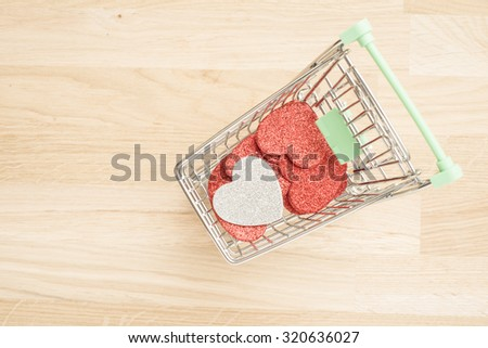 Hearts in shopping cart. Concept of buying love, romance and affection. - stock photo