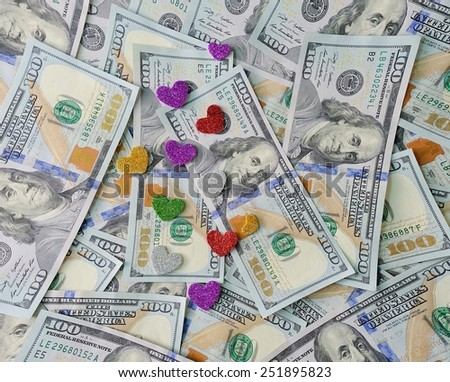 Hearts lie on money dollars, concept of love for money. - stock photo
