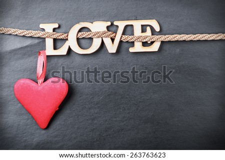 hearts made of felt and the word love made of wood. Can be used for congratulation to the holiday Valentine's Day and Mother's Day - stock photo