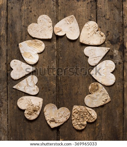 Hearts made of tree bark lying on a weathered old wooden textured table - stock photo