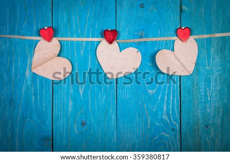 hearts of paper, hearts clothespins on a string, blue wood background, concept of Valentine's Day - stock photo