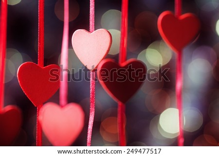 Hearts on red ribbon over abstract defocused lights - stock photo