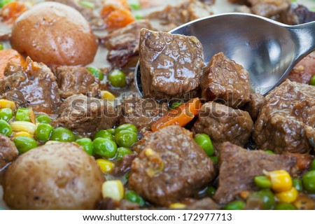 Hearty and traditional beef stew close up, focus on the spoon. - stock photo