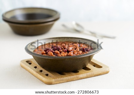 Hearty bowl of slow baked beans in a sauce. - stock photo