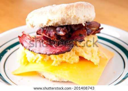 hearty egg, cristpy bacon, cheese sandwich on a homemade buttermilk biscuit - stock photo