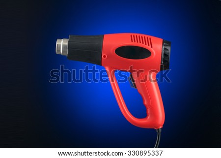 Heat gun with sticker isolated on blue background - stock photo