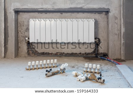 Heating battery and plumbing vents are on the floor in apartment - stock photo