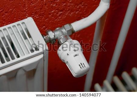 Heating radiator closeup, red wall - stock photo