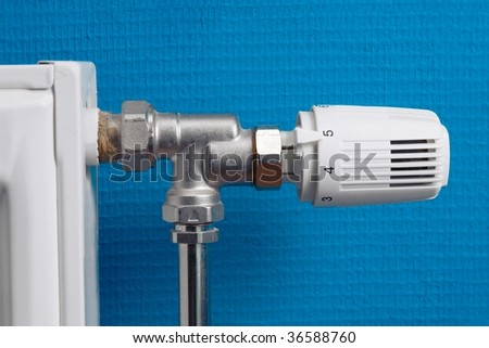 Heating radiator with regulator in front of blue wall - stock photo