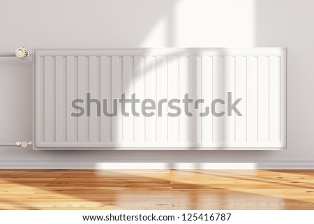 Heating system attached to wall frontal with hardwood floor - stock photo