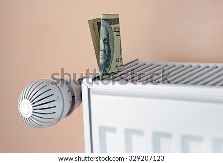heating thermostat with money, hundred dollar, expensive heating costs concept - stock photo