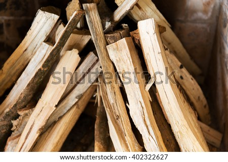 heating, warmth and coziness concept - close up of firewood in fireplace - stock photo