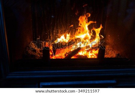 heating, warmth, fire and cosiness concept - close up of burning fireplace at home - stock photo