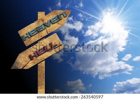 Heaven and Hell - Sign on Blue Sky. Wooden directional sign with two arrows in opposite direction with text heaven and hell on blue sky with clouds and sun rays - stock photo