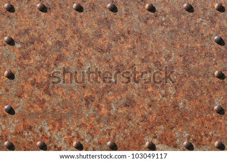 Heavily rusted metal plate, with rusted, riveted edges. / Rusted Steel, Riveted Edges / Great background for text, painting, or whatever your notion. - stock photo