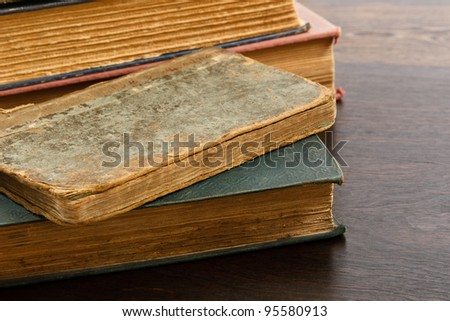 Heavily worn antique books piled on a wood table - stock photo