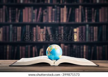 Heavy book and globe - stock photo