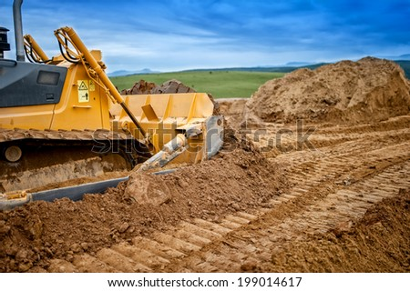 Heavy bulldozer and excavator loading  and moving red sand or soil on road construction site - stock photo