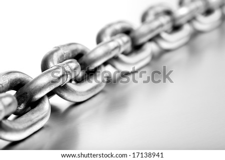 heavy chain on brushed metal - macro with white background - stock photo