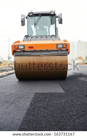 Heavy cibration roller compactor at asphalt pavement works for road repairing - stock photo