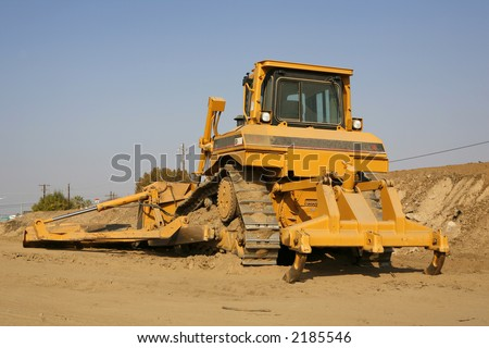 Heavy construction equipment with ripper on one end and blade and blade extension on the other - stock photo