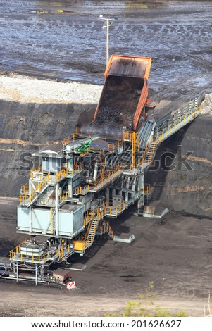 heavy construction tipper trucks dump coal to the conveyor at coal mine - stock photo
