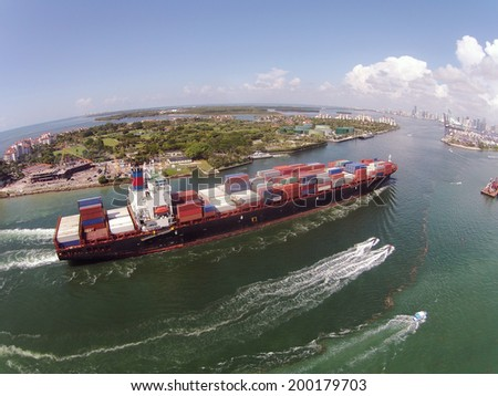 Heavy container ship entering Port of Miami aerial view - stock photo