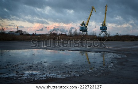 Heavy cranes in harbor with frozen water foreground and dark sunset sky. Can be used as concept for crisis, recession, stagnation, bankruptcy, failure, inactivity, downturn, hard times etc - stock photo