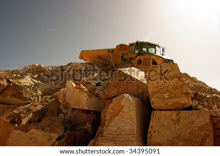 Heavy dump truck against  operating in a marble quarry under strong sun; backlit - stock photo