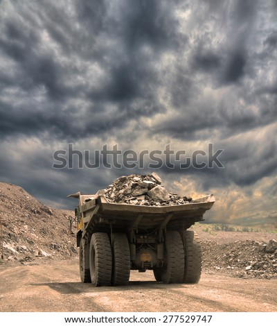 Heavy dump truck with iron ore on the opencast on stormy sunset - stock photo