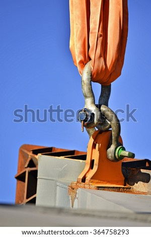 Heavy duty chain hooked up on a construction crane lifting concrete a structure - stock photo