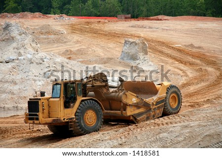 Heavy earth mover at a construction site - stock photo