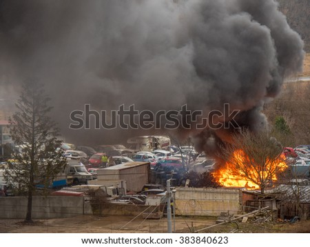 Heavy fire with dark grey black smoke pollution at car service parking. Burning rubber, chemical stuff, blazing bright orange flame. Firefighters extinguished fire fast. Car, building, fuel explosion - stock photo