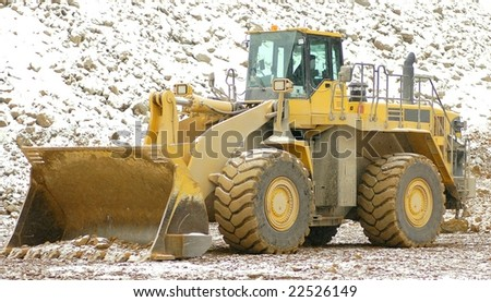 Heavy front loader in open cast mining quarry - stock photo